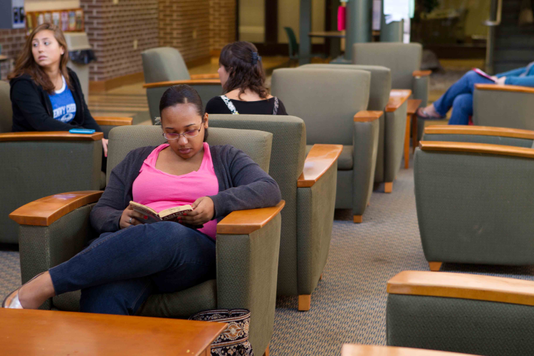student reads in mcgowan atrium chair