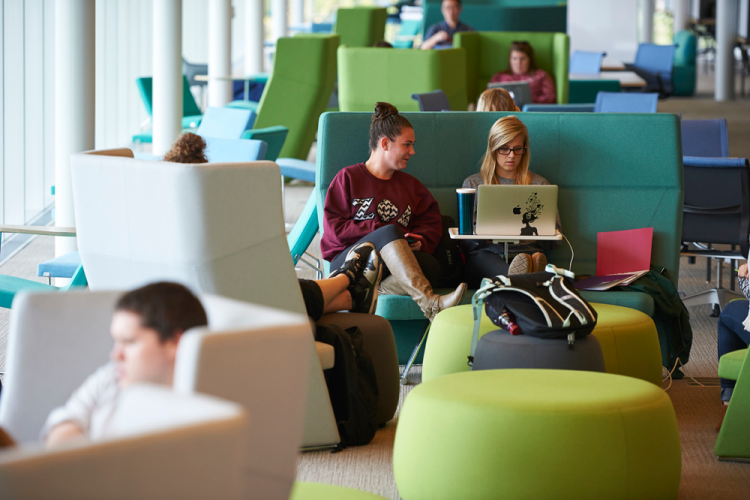 students sit in learning commons on laptop