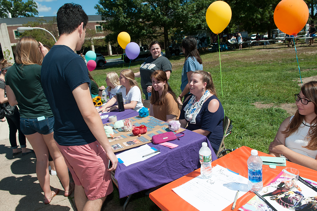 students gather at club fair table