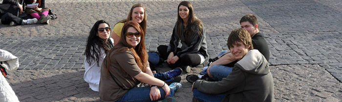 students sitting on cobblestones in spain
